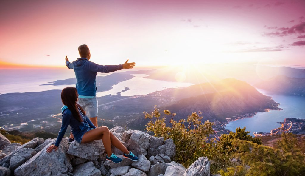 Happy couple watching the sunset in the mountains. Summer travels