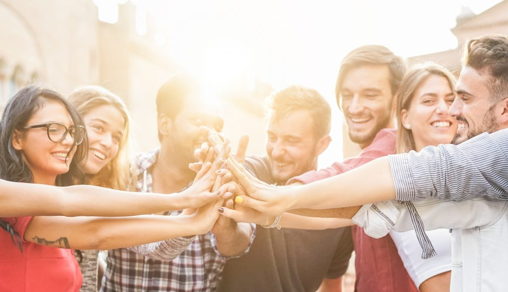Young millennials friends stacking hands together - Happy students celebrating together - Youth lifestyle, university, relationship and friendship concept - Focus on hands